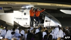 Bertrand Piccard (R) and Andre Borschberg (L), pilots of the solar powered Solar Impulse 2 aircraft, are greeted upon arrival at Al Batin Airport in Abu Dabi to complete its world tour flight, July 26, 2016, in the United Arab Emirates.