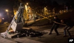 Activists in Poland pull down a statue of a prominent deceased priest, Father Henryk Jankowski, who allegedly abused minors sexually, in Gdansk, Poland, Feb. 21, 2019.
