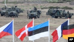 FILE - Flags flutter in front of soldiers taking positions with their army vehicles during the NATO Noble Jump exercise on a training range near Swietoszow Zagan, Poland, June 18, 2015.