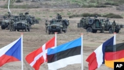 FILE - Flags are seen in front of soldiers with military vehicles during NATO exercises near Swietoszow Zagan, Poland, June 18, 2015. Russia is demanding that the alliance reduce its size in Europe to levels it maintained in 2000.