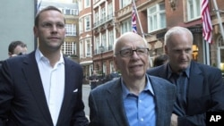 James and Rupert Murdoch (C) and a minder leave the Stafford Hotel in St James's Place, central London July 10, 2011