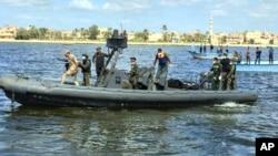 Penjaga pantai dan petugas penyelamatan di Rosetta, Mesir, membawa mayat-mayat yang diambil dari kapal migran yang tenggelam di Laut Tengah (27/9). (AP/Maggie Michael)