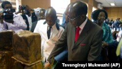 "FILE: Zimbabwe's President Robert Mugabe cuts his birthday cake as he marks his 93rd birthday at his offices in Harare, Tuesday, Feb. 21, 2017. Mugabe described his wife Grace, an increasingly political figure, as ""fireworks"" in an interview marking his 93rd birthday. (AP Photo/Tsvangirayi Mukwazhi)"
