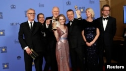 "The cast and crew of ""The Crown"" pose together after winning the Golden Globe award for Best Television Series - Drama as star Claire Foy holds her award for Best Performance by an Actress In A Television Series - Drama, Jan. 8, 2017."