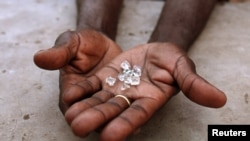 An illegal diamond dealer from Zimbabwe displays diamonds for sale in Manica, near the border with Zimbabwe, September 19, 2010.