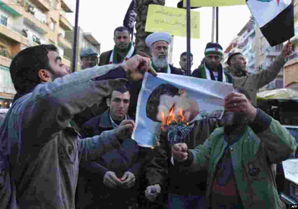 Lebanese anti-Syrian regime protesters, burn a portrait of Syrian President Bashar Assad during a demonstration to show their solidarity with the Syrian people, in the northern city of Tripoli, Lebanon, on Friday Jan. 20, 2102. The Arab League is likely t
