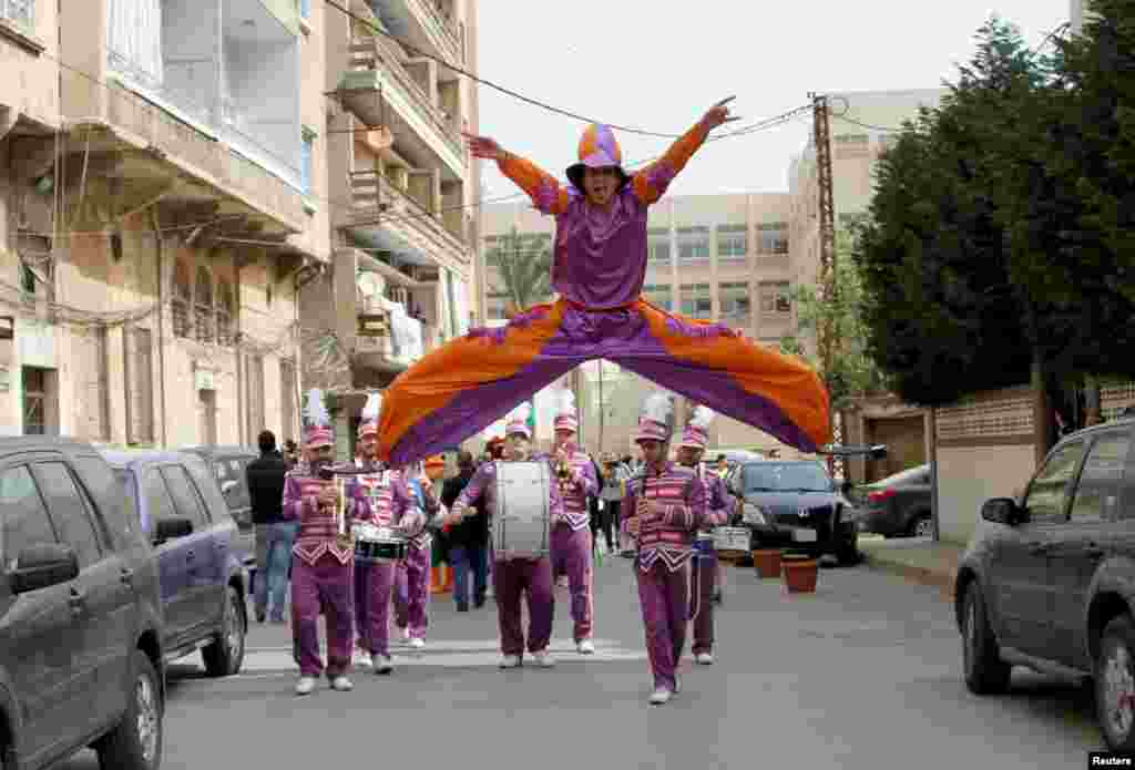 A dancer jumps during a parade celebrating the coming of spring in Tripoli, north Lebanon, April 17, 2015.
