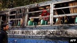 Cảnh sát, nhân viên cứu hộ xem xét hiện trường vụ nổ bom xe buýt chở học sinh ở tây bắc Pakistan, ngày 13/12/2010