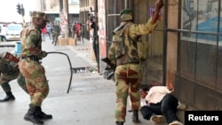 FILE: Soldiers beat a supporter of the opposition Movement for Democratic Change party of Nelson Chamisa outside the party's headquarters as they await the results of the general elections in Harare, Zimbabwe, Aug. 1, 2018.