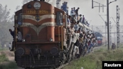 FILE - Passengers travel on an overcrowded train at Loni town in the northern Indian state of Uttar Pradesh. Accidents are common on India's railroad network.