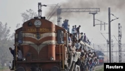 Passengers travel on an overcrowded train at Loni town in the northern Indian state of Uttar Pradesh July 8, 2014.