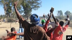 FILE: A rioter wearing a police helmet taken from a police officer joins angry protestors in Harare, Monday, July, 4, 2016.
