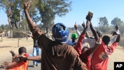 A rioter wearing a police helmet taken from a police officer joins angry protestors in Harare, Monday, July, 4, 2016. (AP Photo/Tsvangirayi Mukwazhi)