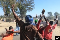 A rioter wearing a police helmet taken from a police officer joins angry protestors in Harare, Monday, July, 4, 2016.