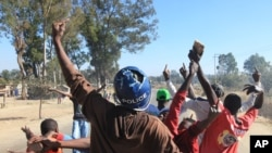 FILE: A rioter wearing a police helmet taken from a police officer joins angry protestors in Harare, Monday, July, 4, 2016.Police in Zimbabwe's capital fired tear gas and water cannons in an attempt to quell rioting by taxi and mini bus drivers protesting what they describe as police harassment.(AP Photo/Tsvangirayi Mukwazhi)