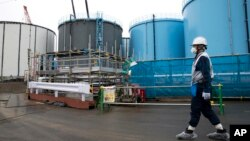 FILE - An employee walks past storage tanks for contaminated water at the tsunami-crippled Fukushima Dai-ichi nuclear power plant of the Tokyo Electric Power Co. in Okuma town, Fukushima prefecture, Japan, Feb. 23, 2017.