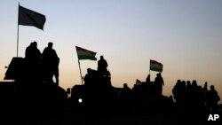 Tentara Permeshga Kurdi berdiri di atas kendaran-kendaraan militer yang bergerak menuju desa-desa di sekitar Mosul, Irak (17/10). (AP/Bram Janssen)