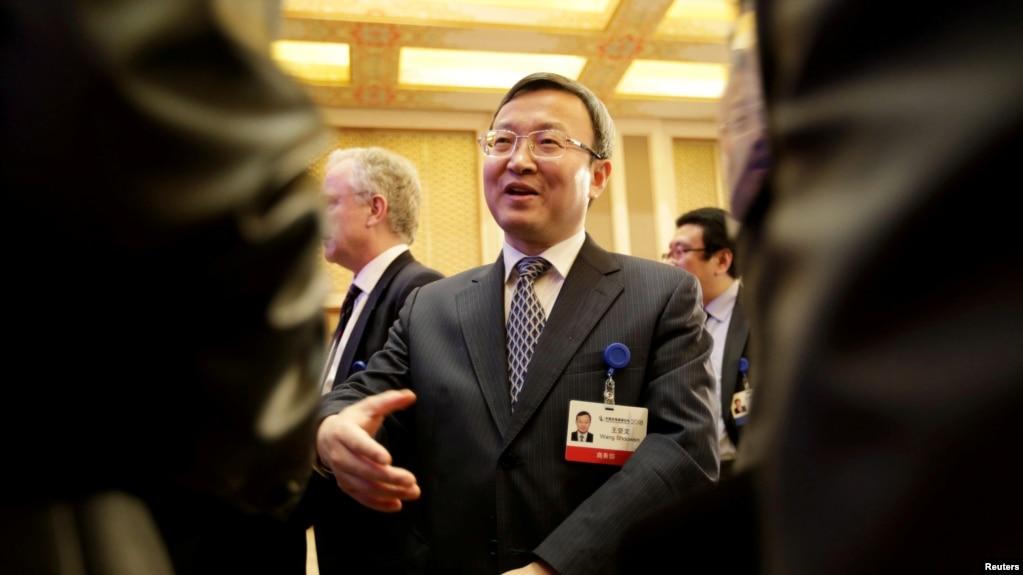 在北京釣魚台國賓館舉行的中國發展論壇(CDF)年會上,中國商務部副部長兼國際貿易談判副代表王受文發表演講後與與會者聊天(2018年3月25日)。
