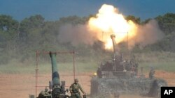 FILE - Members of Taiwan's military fire artillery from self-propelled Howitzers during the annual Han Kuang exercises in Hsinchu, northeastern Taiwan, Sept. 10, 2015.