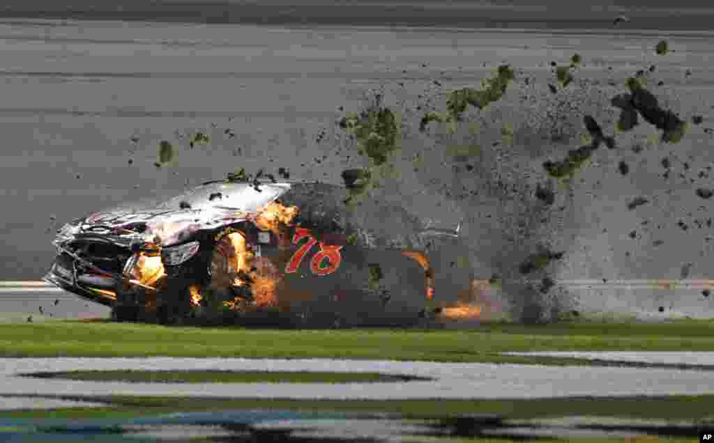 Martin Truex Jr. (78) drives his burning car across the grass after a crash during the second of two NASCAR Sprint Cup series qualifying auto races at the Daytona International Speedway in Daytona Beach, Florida, USA, Feb. 20, 2014.