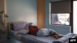 FILE - A TB patient sleeps in his room at the Sizwe Tropical Diseases Hospital in Johannesburg, South Africa, August 5, 2019.