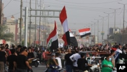 FILE - Anti-government protesters rally outside the provincial council building in Basra, Iraq, May 25, 2021. Iraqis have taken to the streets in several of the country's cities protesting cuts in electricity supplies during scorching summer temperatures.