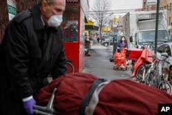 Funeral director Tom Cheeseman retrieves a body on a house call, April 3, 2020, in the Brooklyn borough of New York.