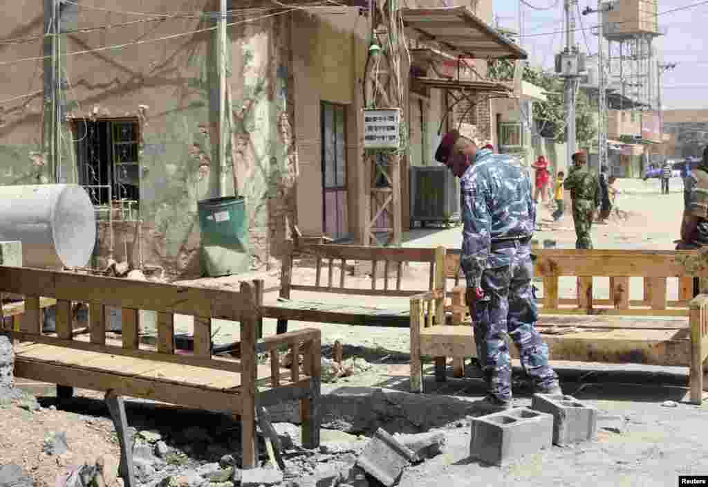 An Iraqi policeman inspects the site of a suicide bombing attack at a coffee shop in the Shi'ite district of the city of Baquba, about 50 kilometers northeast of Baghdad, July 2, 2013.