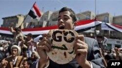 """Участник субботней демонстрации в Сане держит в руках лепешку с надписями на арабском и английском - """"Уходи"""". Адресат пслания - действующий президент Али Абдулла Салех."""