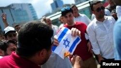 Un Palestinien tient un drapeau d'Israël dans ses mains, à Gaza, le 18 juillet 2014.