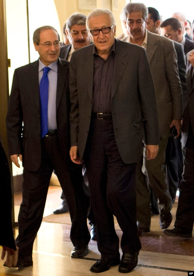 U.N.-Arab League envoy Lakhdar Brahimi (R) and Deputy Syrian Foreign Minister Faisal Mekdad arrive to a hotel surrounded by security, Oct. 28, 2013 in Damascus, Syria.