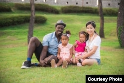 Lily Lee, far right, sits with her family for a portrait. Pictured: James, far left, with their daughters Yuri, center left, and Dasomi, center right.