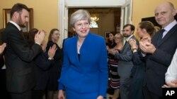 Perdana Menteri Inggris Theresa May disambut oleh staf saat ia kembali ke Downing Street, setelah meminta izin dari Ratu Elizabeth untuk membentuk pemerintahan baru, di London, 9 Juni 2017.
