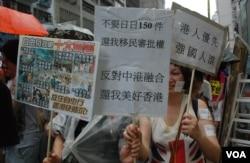 不願意透露姓名的遊行人士(右)手持反對中港融合的標語參加7-1大遊行(美國之音湯惠芸)