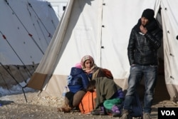 A refugee family waits to leave Presevo, Serbia, for Western Europe, Jan. 19, 2016. (P. Walter Wellman/VOA)