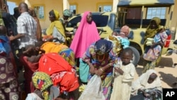 FILE - Women and children rescued by Nigerian soldiers from Boko Haram extremists in northeast Nigeria arrive at the military office in Maiduguri, Nigeria, July 30, 2015.