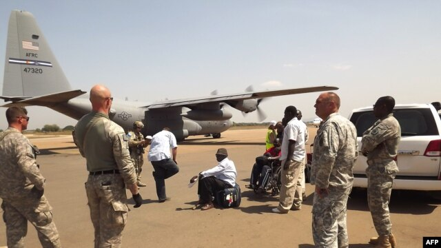 US army soldiers stand guard as a US army aircraft remains on the runway awaiting the arrival of American nationals who are being evacuated due to recent unrest and violence in South Sudan, on December 21, 2013, in Juba.