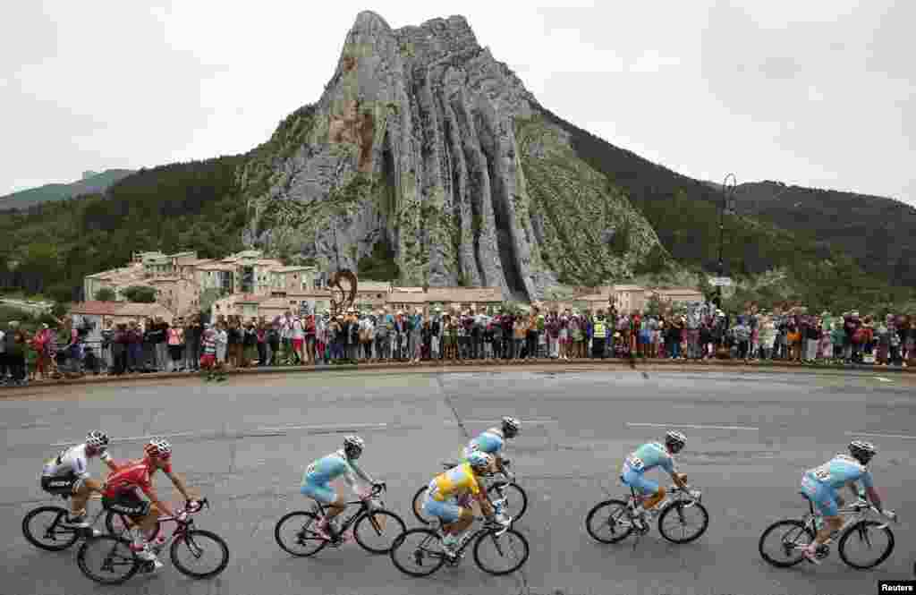 A pack of riders including race leader Astana team rider Vincenzo Nibali (C) of Italy cycles past Sisteron during the 222-km 15th stage of the Tour de France cycling race between Tallard and Nimes.