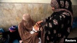 一名女性小儿麻痹症疫苗接种工作者在巴基斯坦白沙瓦的一家医院为儿童注射疫苗。(2012年12月8日)