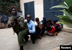 People are evacuated by a member of security forces at the scene where explosions and gunshots were heard at the Dusit hotel compound, in Nairobi, Kenya, Jan. 15, 2019.