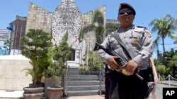 A police officers stands at the memorial of the 2002 Bali bombing site in Bali, Indonesia, Jan. 15, 2016.