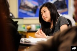 FILE - Sally Kim takes notes during a class in Columbia, Mo. The Common Core approach to math has its critics, who say the method only complicates the subject.
