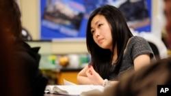 Sally Kim mencatat di sela-sela pelajaran fisika di Columbia Independent School di Columbia, Missouri. Orang tua Kim, yang tinggal di Korea Selatan, mengirim Kim tinggal bersama saudaranya di Columbia untuk mendapatkan pendidikan yang lebih baik. (AP Photo/Grant Hindsley)