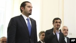 Iranian President Mahmoud Ahmadinejad, right, waves to the media, as he walks up the steps with Lebanese Prime Minister Saad Hariri, prior to their meeting at the Iranian Foreign Ministry, in Tehran, Nov. 28, 2010.