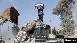 یک عضو ارتش آزاد سوریه، گروه مخالف دمشق مورد حمایت ترکیه، با پائین کشیدن یک مجسمه در عفرین پرچم سوریه را در دست گرفته است.