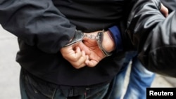 A man in handcuffs who was detained on suspicion of drug trafficking, is escorted by police outside the anti-drug unit of the National Police of Peru in Lima, August 16, 2013. REUTERS/Mariana Bazo (PERU - Tags: CRIME LAW DRUGS SOCIETY) - RTX12OBY