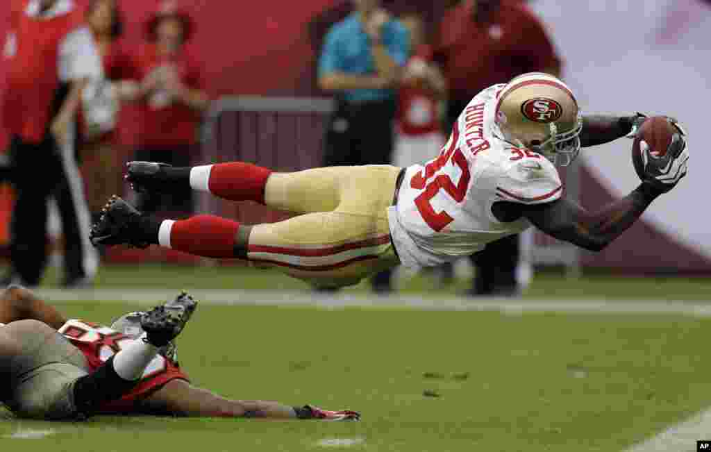 San Francisco 49ers' Kendall Hunter (32) dives into the end zone to score after picking up a fumble by Tampa Bay Buccaneers' Russell Shepard during the fourth quarter of an NFL football game in Tampa, Florida, USA, Dec. 15, 2013.