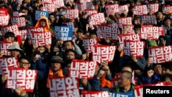 "People chant slogans at a rally calling for President Park Geun-hye to step down in central Seoul, South Korea, Nov. 12, 2016. The placards read, ""Step down Park Geun-hye."""