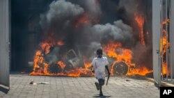 Seorang anak laki-laki berlari menjauh dari sebuah dealer mobil yang dibakar para pengunjuk rasa di Port-au-Prince, Haiti, 17 Maret 2021.