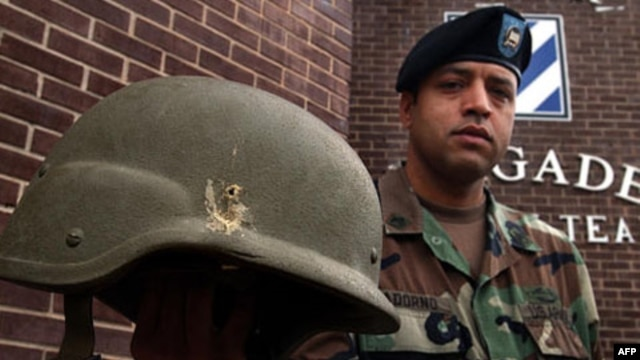 American soldier Jose Adorno holds a Kevlar helmet he was wearing when struck by a grenade explosion in Iraq several years ago